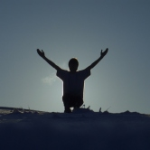Person standing against sky, arms raised in joy